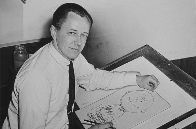 Charles Schulz nel 1956 e un discegno di Charlie Brown (Foto Roger Higgins, World Telegram staff photographer)