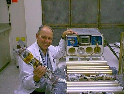 Il Dottor Dennis Morrison assieme al Microencapsulation Electrostatic Processing System usato sulla Stazione Spaziale Internazionale (Foto NASA)